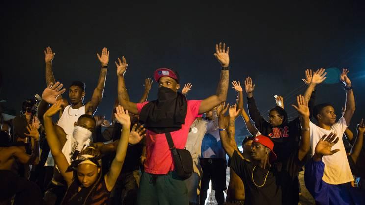 Giovani manifestano con le mani alzate domenica notte a Ferguson